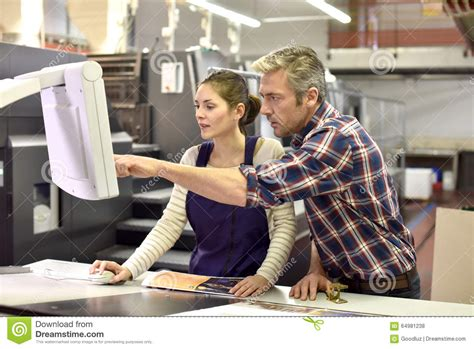 Professional Printer Working With Apprentice Stock Photo